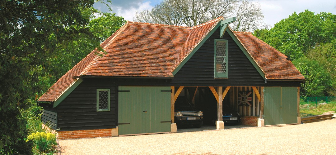Oak Framed Building comprising 4-Bay Garage, Living Space & Storage Areas. Features Stained Weatherboard & Oak Garage Doors crafted in our dedicated joinery workshop